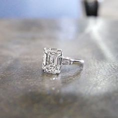 HALLE is a custom, three stones engagement ring set in Platinum with an Emerald cut diamond and two tapered baguettes, from jewelry designer Jean Dousset‼️