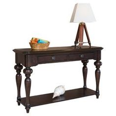 Hand-carved sofa table with turned legs and lower shelf.  Product: Sofa tableConstruction Material: WoodColor: BrownFeatures:  Hand-rubbed patina finish with distressed effectsTwisted legsHand-carved Dimensions: 30 H x 50 W x 18 DCleaning and Care: Wipe with damp cloth