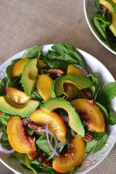 Grilled Peach & Avocado Spinach Salad 2 firm peaches, halved and pitted 1 avocado, halved and pitted 1 clove garlic, mincd 2 tablespoons red wine vinegar ½ teaspoon Dijon mustard ½ teaspoon honey 2 tablespoons olive oil + 1 tablespoon to drizzle on fruit salt 4 cups fresh spinach ¼ cup feta cheese ¼ cup pecan halves, toasted ½ red onion, sliced