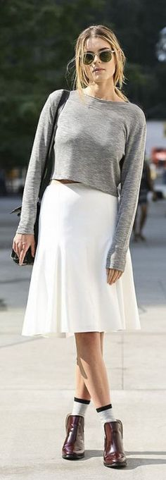 White knee length skirt worn with a cropped grey long sleeve shirt and ankle boots with socks