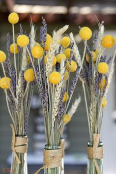 Wheat yellow billy balls and purple lavender in wine bottles as centerpieces
