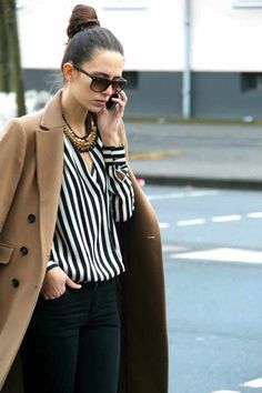 Camel coat on a black and white striped shirt with skinny jeans, a statement necklace, big sunglasses and a sleek top knot.
