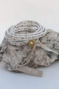 This iconic Chan Luu scalloped wrap bracelet is gorgeous! A mix of quartz and gold beads are hand laced with natural white leather. Gold clasp. Original, unique, and one-of-a-kind!