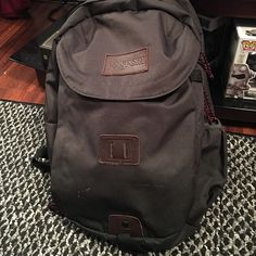 Jansport Dark Grey Backpack has three pockets and the main pocket includes a laptop sleeve. there are two small white marks on the front from it scraping against a wall but other than that its in perfect condition. Jansport Bags Backpacks