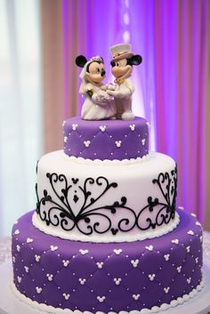 Purple, black and white Disney themed wedding cake. Even with Mickey and Minnie Mouse as the bride and groom cake topper!