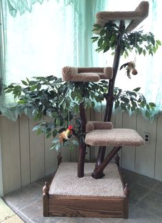 This real wood cat tree is availible and in stock. It offers three padded seats, oak base, leaves, and two attached play toys.
