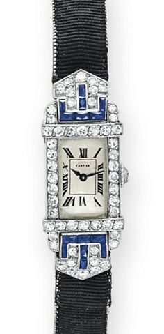 AN ART DECO DIAMOND AND SAPPHIRE WRISTWATCH, BY CARTIER   With mechanical jeweled movement, the rectangular dial with black Roman numerals and blued steel hands, within a single-cut diamond bezel with calibré-cut sapphire detail, to the black satin strap, mounted in platinum and 18k gold, circa 1925, 6 ins., with French assay marks, in a Cartier red leather box  Signed Cartier, nos. 25566, 9806, 15598 and 7724, movement unsigned, movement no. 25566