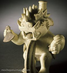 Photograph of a Moche (Mochica) ceramic pot vessels in the form of a decapitator monster or god holding a tumi knife and the decapitated head of a victim or sacrifice. The gruesome scene of ritual killing, torture, and sacrifice is not uncommon in Moche art.