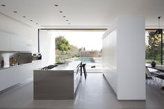 Kfar Shmaryahu House by Pitsou Kedem Architects parede em cimento com armários brancos. Semelhante como roupeiro de hall