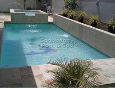 Caribbean Pool and Spa - Construcción de Piscinas en Puerto Rico - piscina con jacuzzi, área verde y mosaicos decorativos al fondo de la piscina