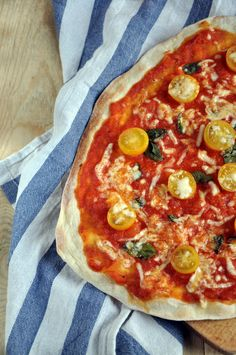 Pizza with yellow cherry tomatoes, basil and mozzarella