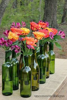 Wine and beer bottles with casual flowers for rehearsal dinner center pieces (decorating ideas for quinceanera)