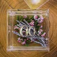 Top view of clear acrylic ring box with rings and decorative accents inside