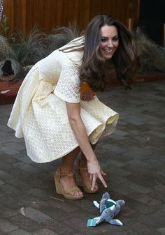 APRIL 20: Catherine, Duchess of Cambridge picks up a toy bilby Prince George of Cambridge threw on the ground as Prince William, Duke of Cambridge holds Prince George of Cambridge during a visit to the Bilby Enclosure at Taronga Zoo on April 20, 2014 in Sydney, Australia.