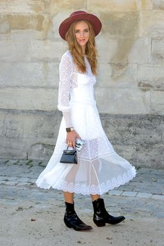 Chiara Ferragni instantly updates her white sundress with a prairie touch courtesy of her black cowboy boots, mini handbag and fedora hat.