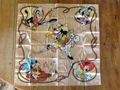 This is a sweet The Walt Disney Company vintage handkerchief or Bandana featuring Mickey Mouse rodeo riding and his friends, Donald Duck, Minnie Mouse, Goofy, and Clarabelle Cow all dressed in western style and having lots of fun. I have not washed or ironed this as I like to leave that up to the buyer. Sorry for the wrinkles, its been in a drawer for many years.