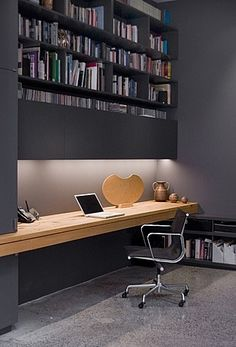 Wonderful way to keep a home office free of clutter: keep all the gubbins within arm's reach, in closed cupboards just above your head.