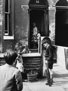 © Shirley Baker  Boy with a Cricket Bat Outside Terraced House - Manchester