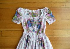 A vintage cotton gown from the late 1930s (possibly early 1940s). This dress has puffed sleeves, a square neckline, waist that has a dropped V in front, gathered skirt, and side snaps. The fabric is semi-sheer, feels like a cotton voile, and has swiss dots and a floral/butterfly print.  Size: xs  Bust: 31-33 Waist: 25 Hip: open Length: 52 Bodice length (to highest part of waist seam): 15  Condition: Excellent  Follow me on Instagram for shop previews: @bluefennel