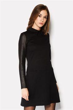 Короткое с волнистой юбкой платье выполнено из французского трикотажа с использованием структурного трикотажа на рукавах. Горловина платья представлена стандартным «рубашечным» воротником.