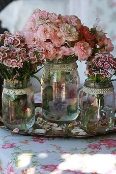 carnations and sweet william in pearl and lace decorated jam jars. so pretty