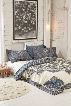 White brick wall and a bohemian style duvet cover.