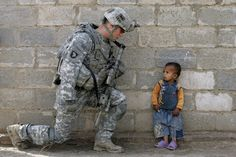 An Iraqi boy looks up a US soldier during a joint air assault with Iraqi soldiers in Al-Rudwaniyah, on the southwest edge of Baghdad, on May 2, 2008. A simple moment, captured by AFP photographer Mauricio Lima, that says so much.