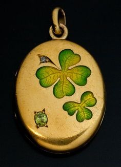 Art Nouveau jeweled gold and enamel locket. French with Russian import marks for 1899-1908. 18K gold, one rose-cut diamond and an oval demantoid garnet. The cover is decorated with two finely painted guilloche enamel clovers.