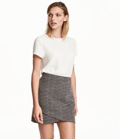 Black/white. Short skirt in jacquard-knit stretch fabric with a wrapover front section and concealed elastication at waist. Unlined.