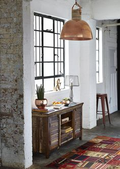 Luxe rustic vibe with exposed wooden sideboard and copper pendant shade