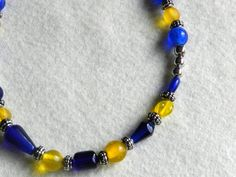This attractive and expensive-looking princess-length (18.25 inch) necklace is hand-strung with lovely dark blue, lapis-blue and frosted saffron-colored glass beads of various shapes. Silver round beads and small decorative beads are dispersed throughout the piece giving it an upscale look. The necklace fastens with an easy-to-close toggle closure. This beautiful piece of jewelry will complement any outfit. Great for the office or for wearing to your favorite sporting event. #etsy #handmade