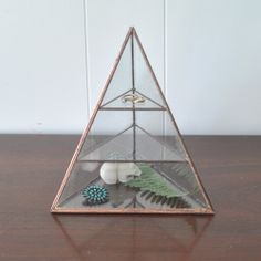 This is one of a series of three large stained glass pyramids. Inspired by the three pyramids at Giza, I created three separate styles, the Vega, Lyra and Polaris. The Lyra Pyramid has a triangle base, 2 shelves and a hinged front door. Available in silver or copper color.I construct these from clear glass and a lead-free, silver alloy solder.Measurements:Width: 7