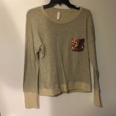 Tan sweatshirt with gold detailing. Tan sweat shirt with gold detailing on the front pocket. Worn once, bought from target by the brand xhilaration. 100% cotton, the sweater is thin, and not very heavy. Xhilaration Sweaters Crew & Scoop Necks
