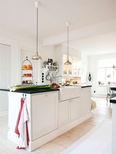 Rustic Scandinavian House In Black And White | soap stone counters, white wooden nobs, industrial pendants
