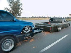 Bagged and body dropped Dually laying frame pulling a trailer with a bagged Taco. Supper Badass!!!!
