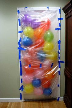 First, loosely tape a clear table cloth or plastic tarp to the door frame. Using painter's tape will help protect surfaces. Start by taping along the bottom and work your way up – remember to leave room for ballons! When you are almost to the top- add the balloons. Secure top with tape. Fun idea