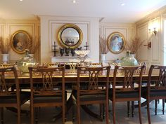 A dining room table from Christie's seats eighteen. The chairs are from The Devon Shop. In the rear wall, black iron urns from Paris stand below a French 19th-century mirror, The French portrait paintings were found at Marché aux Puces.