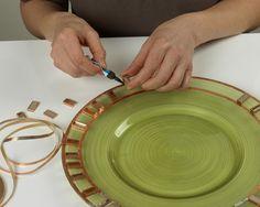 Paso 1) Aplique cinta de cobre autoadhesiva alrededor de los bordes de +/- cuarenta baldosas de mosaico de 20 x 10 mm (para un plato tallado de 30 cm). Luego aplique dos tiras de cinta de cobre alrededor del borde del plato tallado, espaciándolas 20 mm. Pula la cinta utilizando, por ejemplo la parte trasera de una cucharilla. Pegue los mosaicos alrededor del plato de forma que los bordes superior e inferior toquen las cintas, espaciando los mosaicos de manera aleatoria como se muestra.