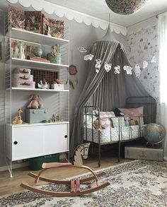 Gentle grey baby's room with a touch of vintage in the old suitcases, globe and floral carpet.