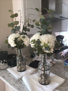 Silk flower arrangements- silver dollar eucalyptus, pussy willow, white hydrangea and ivy with river rocks