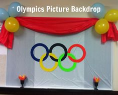 Olympic Picture Background.  All you need is 3 plastic table cloths, 6 balloons, Olympic rings, and two torches.