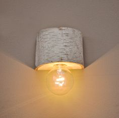 Here's a DIY project: Grab a tree log, a light socket, and a clear light bulb. Drill out the log cavity down the middle and out the back for assembly of the lamp parts. (TIP: If your log isn't wide enough to support a round bulb, use a tubular bulb. It'll keep the light a safe distance from the wall and offer a more industrial look.) Mount and wire directly to an electrical box or invert the fixture and run the cord along the wall to an outlet down below.