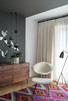 """In a corner of the master bedrooms, a black Greta Grossman Grasshopper lamp sits next to a Bertoia Diamond chair with matching ottoman. Lead designer Chelsie Lee says the Turkish kilim was """"a lucky vintage find."""" A custom Jessica Helgerson cut mirror design is set off by hanging terrariums, made in Vancouver Score + Solder. The American Modern dresser in walnut is from Design Within Reach."""