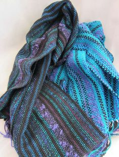 Scarves with a varied texture warp with a solid color weft. Looks nice!