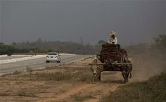 In this March 29, 2013 photo, a car travels in the highway that connects Yangon to capital Naypyidaw as a cart pulled by bulls carry a load in a parallel gravel track, close to Toungoo, north of Yangon, Myanmar. (AP Photo/Gemunu Amarasinghe) ▼10Apr2014AP|Myanmar clunkers scrapped in rush for 'new' cars http://bigstory.ap.org/article/myanmar-clunkers-scrapped-rush-new-cars