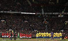 Players and supporters observe the minute's silence