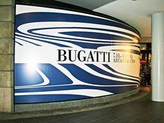 Für die Kunstausstellung -Bugatti Art & Perfection- wurde ein geschwungenes Schaufenster in der Berliner Friedrichstraße in eine riesige Werbefläche verwandelt. In einer Mischung aus Digitaldruck und Folienschnitt entstand eine temporäre Beschriftung, die sich nach Ende der Veranstaltung leicht und rückstandsfrei wieder entfernen ließ.