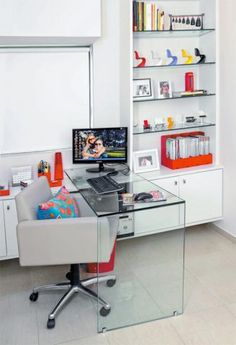 No escritório, a mesa se une à estante, com nichos fechados para equipamentos e documentação e prateleiras que exibem miniaturas de cadeiras. Mesa de vidro. Com 1,40 x 0,55 x 0,80 m e 15 mm de espessura. Vitrieh, 3 x R$ 188,54.
