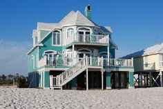 On the beach in Ft. Morgan, AL.  --  I love the turquoise color of this home...and, of course, the sand surrounding the entire home.