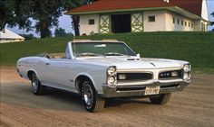 """1966 Pontiac GTO The GTO is one of America's favorite muscle cars. A 1966 redesign gave the car a Coke bottle look, a classic automotive styling cue. The '66 """"Goat"""" was offered as a hardtop coupe, a post coupe and a convertible, and the coupes featured an attractive flying buttress rear roof line. While the 1967 GTO had the same basic look, we prefer the '66 for its louvered taillights.© GM Media Archives"""